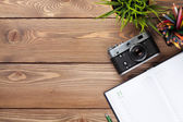 Table with camera, supplies and flower — Stock Photo