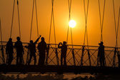 People silhouettes on bridge over sunset — Photo