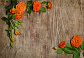 Corners from roses with leaves on wooden background. — Zdjęcie stockowe