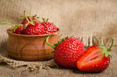 Ripe Strawberry in a wooden Bowl on burlap background — 图库照片