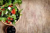 греческий салат в деревянная салатница на столе — Стоковое фото