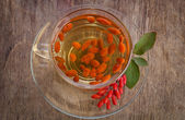 Goji fresh antioxidant tea in glass cup and barberries in wooden — Stock Photo