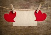 Two Red fabric hearts with sheet of paper hanging on the clothes — Stock Photo
