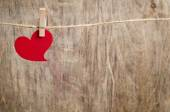 Red fabric heart hanging on the clothesline — Stock Photo