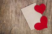Two Red fabric hearts with sheet of paper on old wooden background — Stock Photo