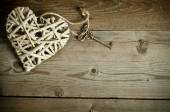 Wicker heart handmade with the key lying on a wooden base — Stockfoto