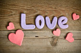 Word Love composition on the wooden board and lots of hearts — Stock Photo
