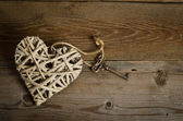 Wicker heart handmade with the key lying on a wooden base . top  — Foto Stock