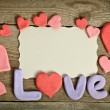 Word Love composition on the wooden board surface and many heart — Stock Photo #63898967