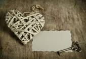 Wicker heart handmade with the key lying on a wooden base with a — Stock Photo