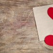 Two Red fabric hearts with sheet of paper lying on old wooden ba — Stock Photo #64428357