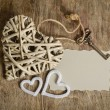 Wicker heart handmade with the key and two small hearts lying on — Stock Photo #64428375