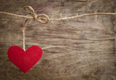 Red fabric heart hanging on the clothesline. On old wood backgro — Stock Photo
