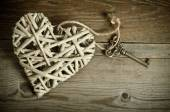 Wicker heart handmade with the key lying on a wooden base . top  — Stock Photo