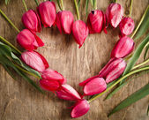 Heart-shaped frame of fresh tulips laying on an old rustic woode — Photo