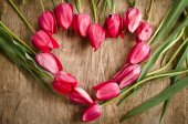 The heart-shaped frame of fresh tulips is laying on an old rusti — Stock Photo