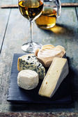 Various types of cheese and white wine — Stock Photo