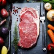 Food background with fresh vegetables and raw beef steak — Stock Photo #57639399