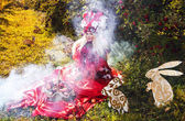 Fashion image of sensual girl in bright red fantasy stylization. Outdoor fairy tale art photo. — Stock Photo