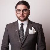 Elegant young handsome man in grey costume. Studio fashion portrait. — Stock Photo