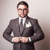 Elegant young handsome man in grey costume. Studio fashion portrait. — Stockfoto