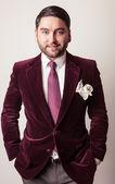 Elegant young handsome man in luxury velvet claret costume. Studio fashion portrait. — Stock Photo