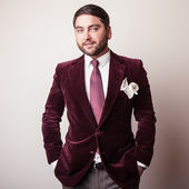 Elegant young handsome man in luxury velvet claret costume. Studio fashion portrait. — Foto de Stock
