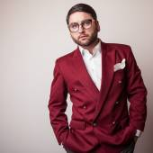 Elegant young handsome man in luxury red costume. Studio fashion portrait. — Stock Photo