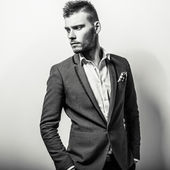 Elegant young handsome serious man in classic costume. Black-white studio fashion portrait. — Stock Photo