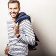 Elegant young handsome & positive man with dark blue jacket. Bright studio fashion portrait. — Stock Photo #70826699