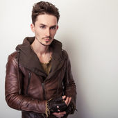 Attractive young man in a brown leather jacket pose in studio. — Stock Photo