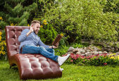 Young handsome man in casual clothes sit in luxury sofa with iPad in summer garden. — 图库照片