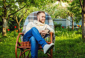 Handsome man relax in rocking-chair with plaid in a summer garden. — Stok fotoğraf