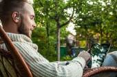 Friendly man sits in a rocking-chair with plaid & tablet in summer country garden. — Stock Photo