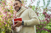 Young friendly man with red book in a summer garden at sunset. — Stock Photo