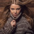 Young attractive girl in a brown sweater poses on wooden background. — Stock Photo #77266992