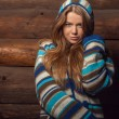 Young attractive girl in a colorful sweater poses on wooden background. — Stock Photo #77267222