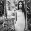 Outdoors portrait of beautiful young brunette girl in luxury dress posing in summer garden.Black-white photo. — Stock Photo #77276056
