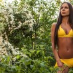 Suntanned attractive beauty dressed yellow bikini poses in autumn garden. — Zdjęcie stockowe #77278610