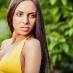 Suntanned attractive beauty dressed yellow bikini poses in autumn garden. — Zdjęcie stockowe #77279036