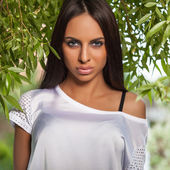 Outdoors portrait of beautiful young brunette girl in white silk shirt posing in summer garden. — Stock Photo