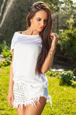 Outdoors portrait of beautiful young brunette girl in white silk shirt posing in summer garden. — Foto Stock