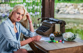 Beautiful young blonde sits in arbor at oak table near vintage typewriter. — Stock Photo