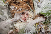 Fairy tale girl portrait surrounded with natural plants and flowers. Art image in bright fantasy stylization. — Stock Photo