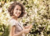 Outdoors portrait of positive young woman in overalls which posing in solar summer garden. — Stock Photo