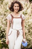 Outdoors portrait of positive young woman in overalls which posing in solar summer garden. — Stok fotoğraf