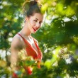 Outdoors portrait of beautiful young brunette girl in luxury red dress posing in summer garden. — Stock Photo #77655618