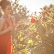 Outdoors portrait of beautiful young brunette girl in luxury red dress posing in summer garden. — Stock Photo #77657102