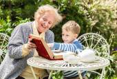Positive grandmother and grandson spent time together in summer solar garden. — Stock Photo