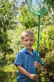 Outdoor portrait of happy little boy with net for butterflies posing in summer garden. — Stock Photo